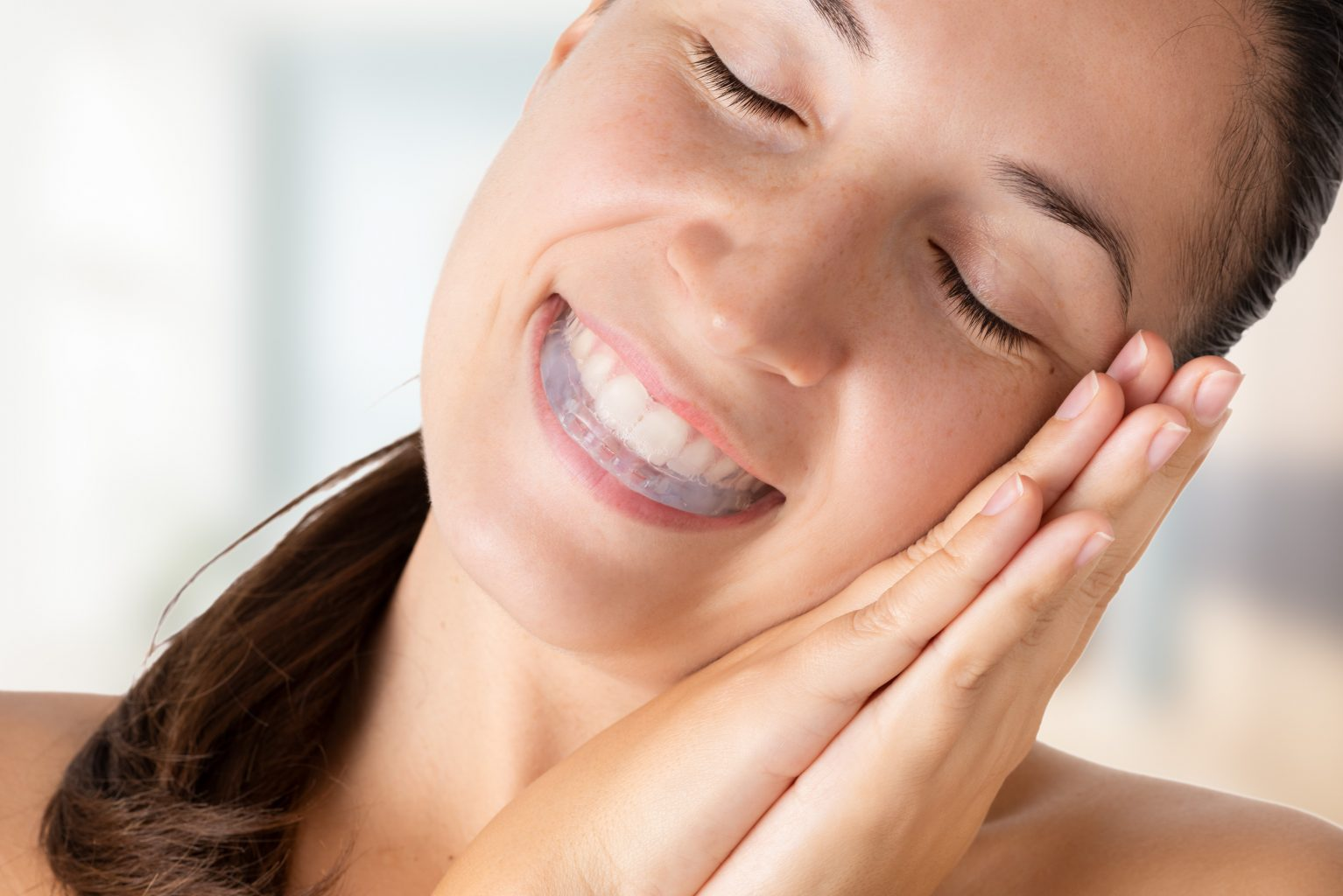 young woman making sleep gesture and wearing bite plate in mouth to save teeth from grinding caused by bruxism. woman sleeps peacefully thanks to the bite plate that protects her teeth from bruxism.